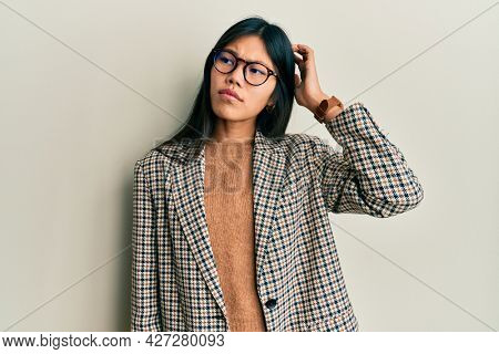 Young chinese woman wearing business style and glasses confuse and wondering about question. uncertain with doubt, thinking with hand on head. pensive concept.