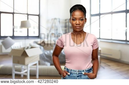 moving, real estate and people concept - african american young woman over new home background