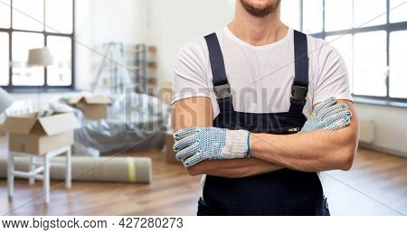 moving, repair and people concept - close up of male worker, loader or repairman in overall and gloves over new home background