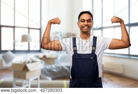 moving, repair and people concept - happy smiling indian worker, loader or repairman showing his power over new home background