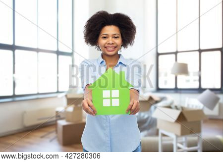 moving, real estate and people concept - happy smiling african american young woman with green house icon over new home background