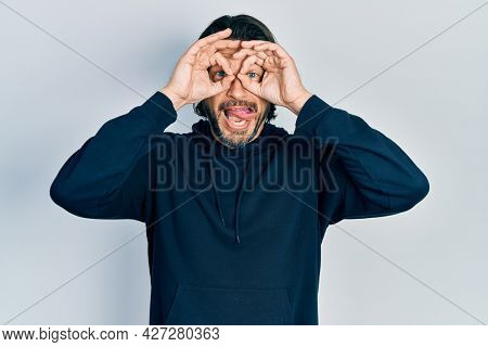 Middle age caucasian man wearing casual sweatshirt doing ok gesture like binoculars sticking tongue out, eyes looking through fingers. crazy expression.