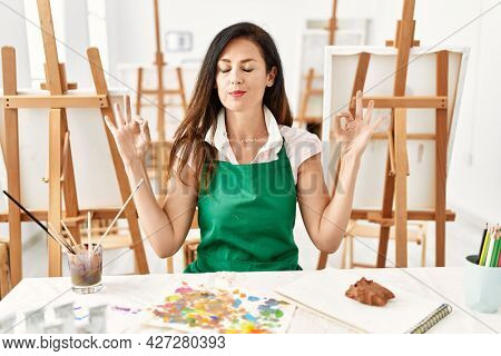 Beautiful caucasian woman at art studio relax and smiling with eyes closed doing meditation gesture with fingers. yoga concept.