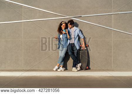 Young Stylish Couple Scrolling Social Media App In Smartphone Look On Mobile Phone Screen Happy Smil