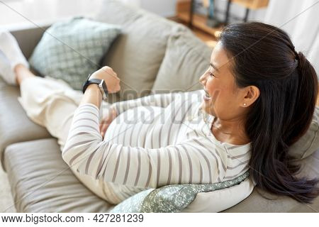 pregnancy, rest, people and expectation concept - happy smiling pregnant asian woman with smart watch sitting on sofa at home
