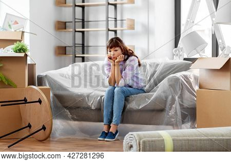 people, repair and real estate concept - sad asian woman with stuff moving to new home