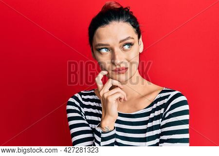 Young caucasian woman wearing casual clothes thinking concentrated about doubt with finger on chin and looking up wondering