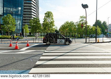 Shinjuku City, Tokyo, Japan - June 12, 2021: Tokyo 2020 Olympic Games. Toyota Taxi Car Passing In Fr