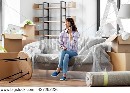 moving, people and real estate concept - happy smiling asian woman with boxes calling on smartphone at new home
