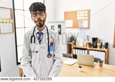 Hispanic man with beard wearing doctor uniform and stethoscope at the office making fish face with lips, crazy and comical gesture. funny expression.