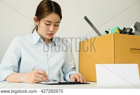 A Woman Office Worker, Dissatisfied With The Termination, Packs Her Belongings In A Cardboard Box An