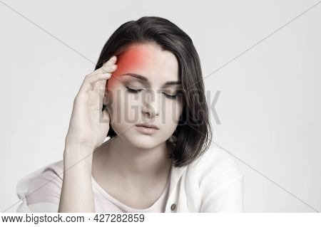 Tired Sad Brunette Woman Touches Her Head, Migraine, Pain Area Of Red Color. Headache Concept.
