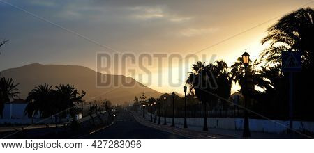 Road With Lamps, Palm Trees And A Tropical Sunset Over The City Of Corralejo And The Red Mountain On