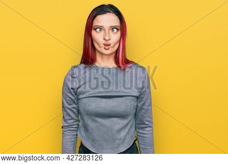 Young caucasian woman wearing casual clothes making fish face with lips, crazy and comical gesture. funny expression.