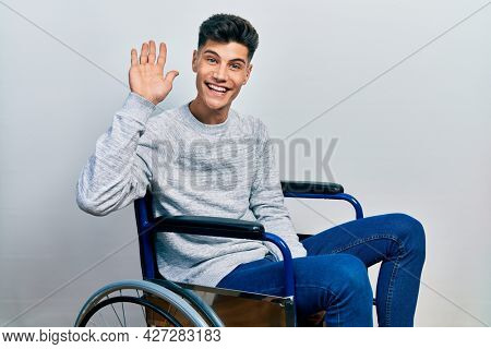 Young hispanic man sitting on wheelchair waiving saying hello happy and smiling, friendly welcome gesture