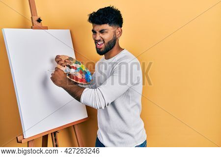 Arab man with beard standing drawing with palette by painter easel stand angry and mad screaming frustrated and furious, shouting with anger. rage and aggressive concept.