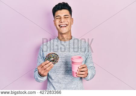 Young hispanic man eating doughnut and drinking coffee smiling and laughing hard out loud because funny crazy joke.