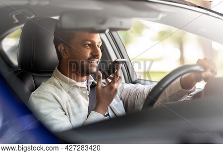 transport, people and technology concept - smiling indian man or driver driving car and recording message using voice command recorder on smartphone