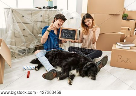 Young caucasian couple with dog holding our first home blackboard at new house pointing fingers to camera with happy and funny face. good energy and vibes.