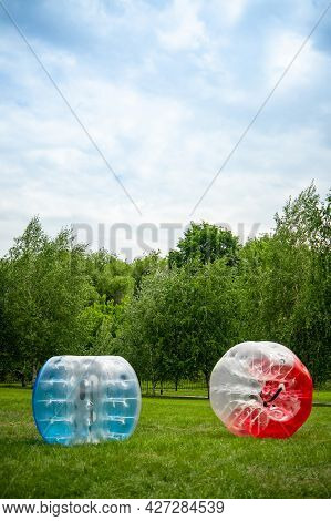 2 Zorbing Balloon On The Summer Lawn. Inflatable Zorb Ball Outdoor. Leisure Activity Concept With Ve