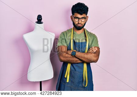 Arab man with beard dressmaker designer wearing atelier apron depressed and worry for distress, crying angry and afraid. sad expression.