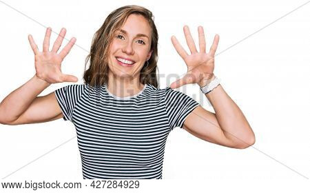 Young blonde woman wearing casual clothes showing and pointing up with fingers number ten while smiling confident and happy.