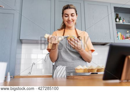 culinary, bake and cooking food concept - happy smiling young woman with baking bag making cupcake topping on kitchen at home