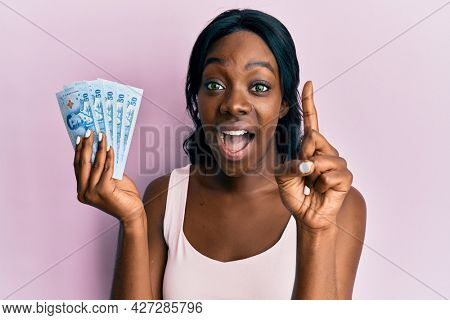 Young african american woman holding thai baht banknotes smiling with an idea or question pointing finger with happy face, number one