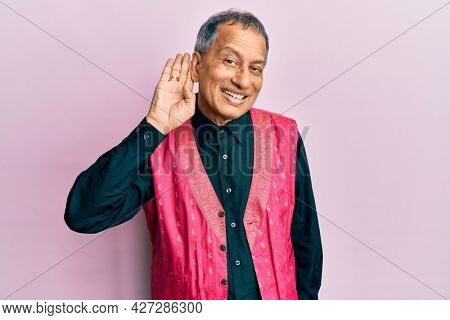 Middle age indian man wearing traditional indian clothes smiling with hand over ear listening an hearing to rumor or gossip. deafness concept.