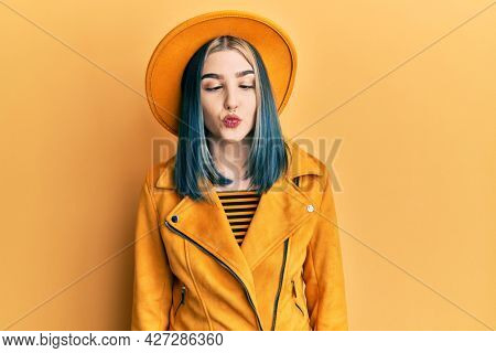 Young modern girl wearing yellow hat and leather jacket making fish face with lips, crazy and comical gesture. funny expression.