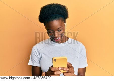 Young african american girl using smartphone and earphones smiling and laughing hard out loud because funny crazy joke.