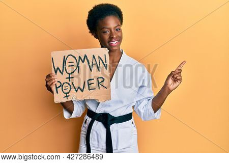 Young african american girl wearing karate kimono holding woman power banner smiling happy pointing with hand and finger to the side