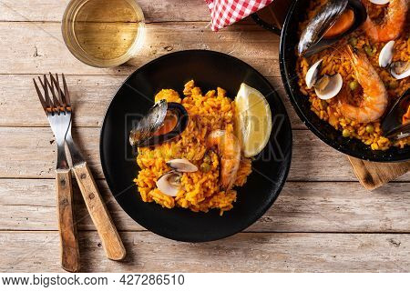 Traditional Spanish Seafood Paella On Wooden Table. Top View