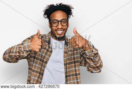Young african american man with beard wearing casual clothes and glasses success sign doing positive gesture with hand, thumbs up smiling and happy. cheerful expression and winner gesture.