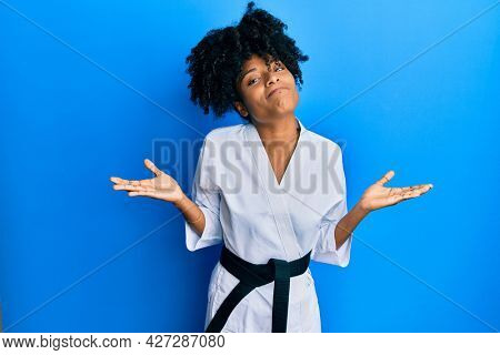 African american woman with afro hair wearing karate kimono and black belt clueless and confused expression with arms and hands raised. doubt concept.
