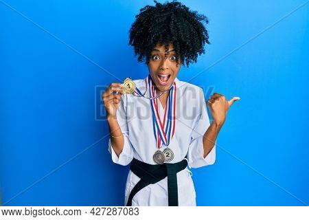 African american woman with afro hair wearing karate kimono and black belt holding medals pointing thumb up to the side smiling happy with open mouth