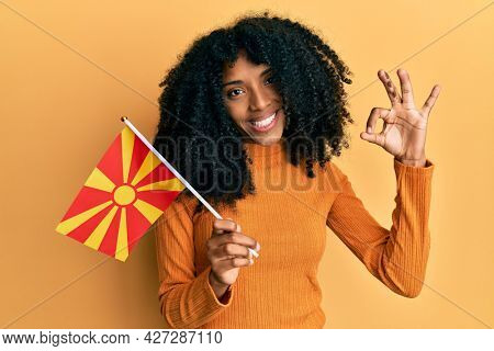 African american woman with afro hair holding macedonia flag doing ok sign with fingers, smiling friendly gesturing excellent symbol
