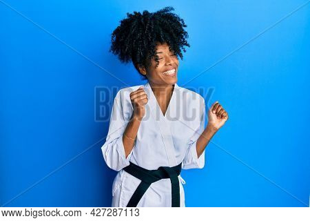 African american woman with afro hair wearing karate kimono and black belt excited for success with arms raised and eyes closed celebrating victory smiling. winner concept.