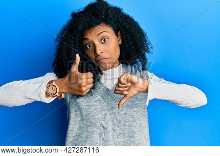 African american woman with afro hair wearing casual winter sweater doing thumbs up and down, disagreement and agreement expression. crazy conflict