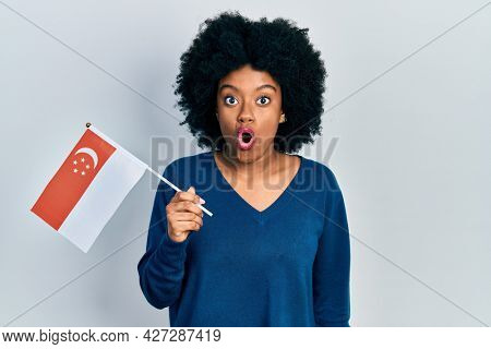 Young african american woman holding singapore flag scared and amazed with open mouth for surprise, disbelief face