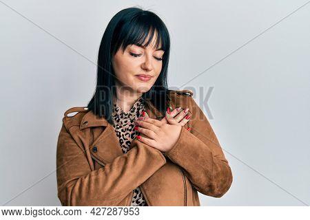 Young hispanic woman wearing casual leather jacket smiling with hands on chest, eyes closed with grateful gesture on face. health concept.