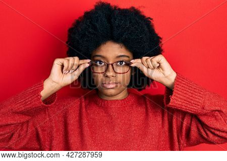 Young african american woman wearing glasses relaxed with serious expression on face. simple and natural looking at the camera.