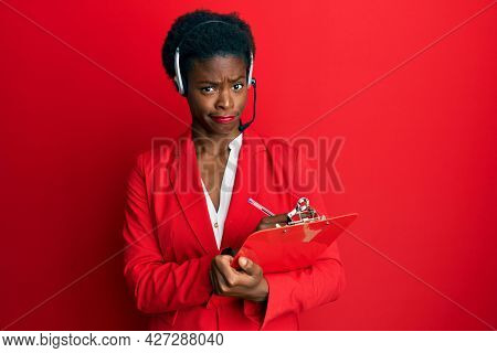 Young african american girl wearing call center agent headset writing on clipboard skeptic and nervous, frowning upset because of problem. negative person.
