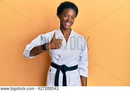 Young african american girl wearing karate kimono and black belt doing happy thumbs up gesture with hand. approving expression looking at the camera showing success.