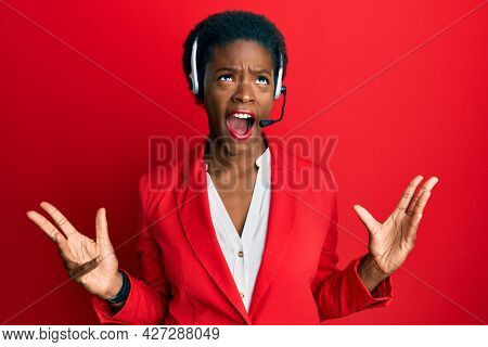 Young african american girl wearing call center agent headset crazy and mad shouting and yelling with aggressive expression and arms raised. frustration concept.