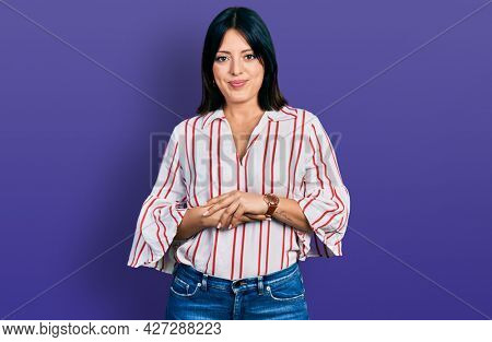 Young hispanic girl wearing casual clothes with hands together and crossed fingers smiling relaxed and cheerful. success and optimistic