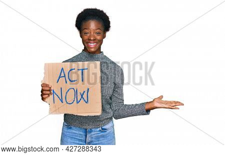 Young african american girl holding act now banner celebrating victory with happy smile and winner expression with raised hands