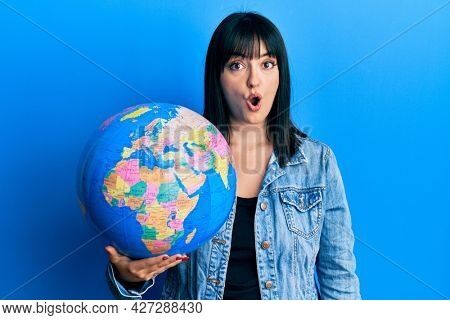 Young hispanic woman holding world ball scared and amazed with open mouth for surprise, disbelief face