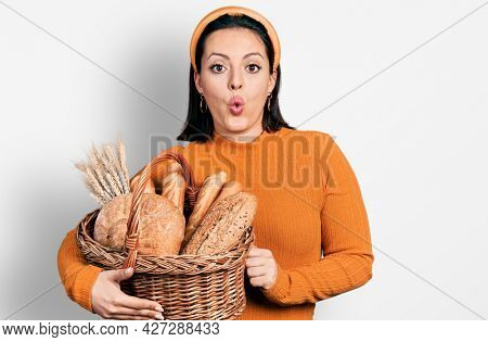 Young hispanic girl holding wicker basket with bread scared and amazed with open mouth for surprise, disbelief face