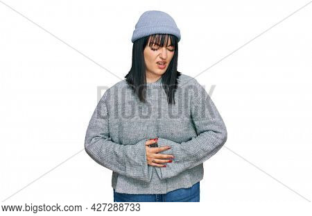 Young hispanic woman wearing cute wool cap with hand on stomach because nausea, painful disease feeling unwell. ache concept.